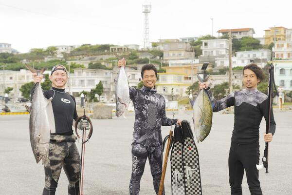 地元漁師と魚を掲げる高田さん