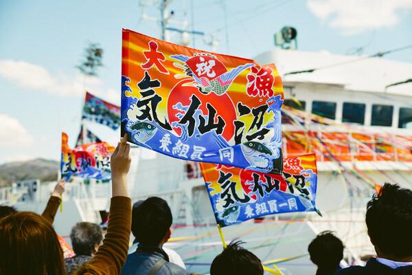 船へとつながる紙テープと大漁旗で漁港はカラフルに