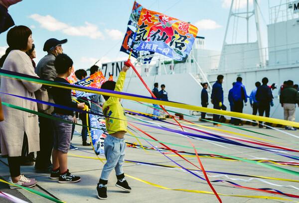 ジャンプしながら旗を振る少年