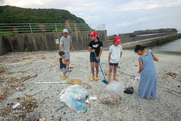 慣れた手つきで細かい漂着ゴミを掃く子どもたち